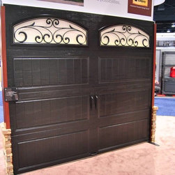 International Builders Show 2014 - Clopay Gallery Collection carriage house style steel garage door in new factory-painted black. Optional decorative windows in many styles, including wrought iron design shown. Solid doors also available.