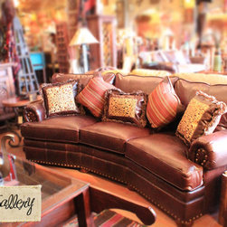 Curved Leather Conversational Sofa - A top grade leather sofa with stud accents. A timeless piece.