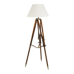 "Campaign Tripod Lamp - The campaign tripod lamp measures 24"" x 24"" x 30.75"". This lamp is UL/CE approved. It comes with a cream fabric shade  is height adjustable. The mud and sandstone walls hid the multistory palace of Imam Yahya, built in the 1930s. From one of the terraces where we were invited to dine in the evening we could look down some 1000 feet into the valley and the lights of the village. The floor was covered with bright carpets, pots with plants were everywhere, and the light came from candles set on tripods. Over chicken and lamb with lentils, followed by cake and cardamom tea, the Imam explained that the tripods were left by a British surveying expedition in the twenties, mapping the deserts and hills of Yemen. We were impressed by the fact that the metal and wood, combined with saddler's leather straps, still looked fresh and new, obviously a combination of quality and form follows function."