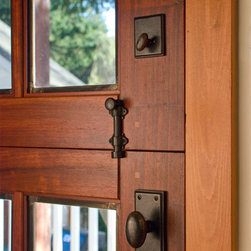 Dutch Doors - Hardware detail of custom dutch doors. Typically a deadbolt is required for the top panel, a dutch cane bolt to secure the panels together, and a passage knob for the bottom panel. These doors are made from Padauk solid wood and feature beautiful leaded glass.