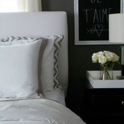 A Blissful Bedroom - A chic bedroom designed by Kristin of Bliss At Home. A crisp white duvet paired with gorgeous shades of gray and a deep gray wall makes for a very relaxing space.