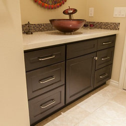 Bathroom remodels by Kitchens Etc. - HomeCrest cabinetry in Maple wood with a Java Finish.