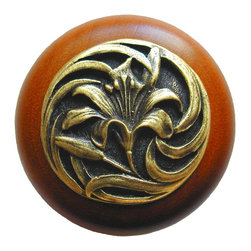 """Inviting Home - Tiger-Lily Cherry Wood Knob (antique brass) - Tiger-Lily Cherry Wood Knob with hand-cast antique brass insert; 1-1/2"""" diameter Product Specification: Made in the USA. Fine-art foundry hand-pours and hand finished hardware knobs and pulls using Old World methods. Lifetime guaranteed against flaws in craftsmanship. Exceptional clarity of details and depth of relief. All knobs and pulls are hand cast from solid fine pewter or solid bronze. The term antique refers to special methods of treating metal so there is contrast between relief and recessed areas. Knobs and Pulls are lacquered to protect the finish. Alternate finishes are available. Detailed Description: A very detailed and beautiful knobs are the Tiger Lily knobs. They are very delicate and bears a lot of positive history. The Tiger Lily is an orange flower that is covered in spots. It has been a useful medical remedy for many centuries. Its scent is said to suppress aggressive behavior and promotes overall good feeling. The smell is said as a superstition to give whoever smells it freckles."""