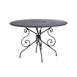 Fermob - 1900 Round Table - Large - Fermob - 1900 is one of the oldest collections from Fermob, a romantic range, featuring the handiwork of a blacksmith. It tells the tales of the early 20th century gardens in the French countryside. Tabletops and seats made from perforated lacquered steel. Available in all Fermob colors. The 1900 Table is 46 inches in diameter and is made of lacquered steel that has a very high protection cataphoresis finish making it good for outdoor use. The scrolls and rings are still hand forged by a blacksmith in France. The table top is perforated and includes a parasol hole. Pairs beautifully with both the 1900 Stacking Side Chair and 1900 Stacking Arm Chair. Fermob furniture undergoes several stages of rust proofing followed by two paint stages: a Fermob exclusive process in one of the most efficient plants in Europe. The paint is a DuPont powder, 100 percent polyester, anti UV, deposited electrostatically on the furniture for optimal coverage, then baked at 193 degrees, just like in the car industry. Ecological paint protects both the environment and your health: the powder paints used by Fermob contain no solvents. They are 100 percent recyclable and are recycled in a zero waste installation.