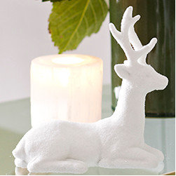 Snowy Reindeer - New - This serene reindeer gazes around the room, the picture of relaxation—and everyone can use a little more serenity during the holidays. He's the perfect size for a tablescape in the kitchen—always a place that could use a harmonious touch. Made with glass glitter, so handle with care.