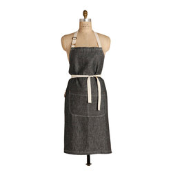 Birdkage - Monterey Classic Bib Apron - The casual cool of cotton linen is given an edge of sophistication in a handsome black color that shows the grain of the cloth just like washed denim. Long enough and roomy enough to be worn by a man or a woman, it can easily be traded off in the kitchen. The classic bib style includes a front pocket with blue jean rivets and is complemented by contrasting cream stitching and cotton ties.