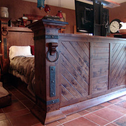 "Custom Beds - Cowboy King Bed: This unique and beautiful king size bed with all the details and an electronic lift within the footboard for up to a 50"" TV…..a 40"" was used within the bed. Complete with custom hand forged ironwork, hand carved corbels, rustic knotty alder hardwoods, and captains drawers for additional storage. If you tap the iron straps on the headboard columns, hidden reading lights come on with a 3 stage dimmer control within the headboard. Finished with an antique distressed finish to give that old world aged appearance"