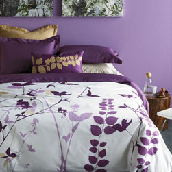 "Amanda Purple Duvet Set - Our Amanda duvet covers interpret botanical motifs in modern graphic silhouettes. Entwined reeds, vines and tall flowers appear in purple and taupe tones—on a crisp white background of 300 thread count cotton sateen. Set includes duvet cover and two solid-color pillow shams with 2"" flange detail. Duvet cover reverses to solid purple. Also available in green colorway."