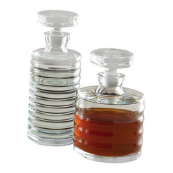 Ribbed Decanter, Small - This shorter version of the simple and appealing Ribbed Decanter has charming proportions accented by three horizontal bands worked into the crafting of the clear glass bottle. Equipped with its own stopper that is nearly as wide as the bottle for a friendly feel in the hand and a horizontal look in your sideboard tablescape, the traditional glass decanter keeps liquor perfectly stored within an attractive vessel. Pair with the taller Ribbed Decanter for best effect.