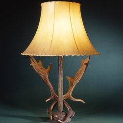 The Gentry Lamp - A pair of European Fallow Deer antlers gracefully mounted on an antiqued cast brass base is shown with the optional medium rawhide shade and is the perfect accent for a sophisticated décor.