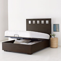 Pivot Storage Bed Frame - Hide and sleep. Easy lift-up frame reveals expansive storage below for off-season items, extra bedding and more. Wide wood rails and short square feet give the frame a monumental look in any bedroom.