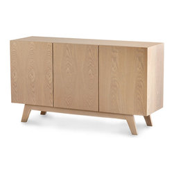Stevens Media Cabinet - Absolutely unadorned in line except for the sharp, precise artisan angle of its legs, the Stevens Media Cabinet is the work of a designer unafraid to appreciate pure geometry. Blocky but softened by the organic feel of its light, natural wood grain, this cabinet has convenient openings at the back for feeding cords and provides low, long storage along a wall.
