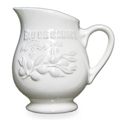 Cuisine De Provence Pitcher - With an attractive angled mouth and wide body, the Cuisine de Provence Pitcher adds naturalistic olive branches and a striking crest to the motifs of your tableware. Glazed in pure white with a hint of antiquing, this stunning ceramic piece offers a serene focal point to your breakfast table and a warm, inviting presence when you're serving iced tea or cocktails.