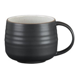 """18th St. Mug - Modern and restrained in form, expressive and rustic in glaze. The artisan's hand is authentically reproduced in this stoneware pattern designed exclusively for Crate and Barrel by ceramic artist and designer Kathy Erteman at her 18th Street studio in New York City. A contemporary matte black exterior contrasts the rustic beauty of a shiny, speckled white glazed interior ringed with the subtly raised spiral associated with hand-thrown pieces. A raised clay rim features a sandy glaze that evokes the feel of exposed terra cotta. To capture the artisan look of this dinnerware, Erteman modeled prototypes to true scale by hand with her original glazes as reference for production. In the words of the designer, """"When making tableware, I consider design and the rigors of daily use. The spirit of my hand in these pieces is modest, to harmonize with and act as a support to the prepared ingredients."""""""
