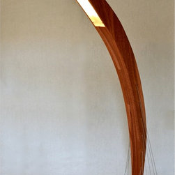 Arc Floor Lamp - The Arc floor lamp takes the concept of the Signature and Peering desk lamps to a whole new level. Standing at 5 ft tall, the lamp is comprised of a mahogany curve that is carefully perched atop a red oak base and held in place only by steel cables under tension. Along with being a functioning lamp, the piece doubles as a beautiful sculpture that is a study in carefully achieved balance. Though the central curve leans away from the base in a suggestion of imminent movement, the lamp is completely stable and sits firmly on the ground. The lamp is perfect for curling up under and reading a book, as the curve will reach gently over a couch or armchair to provide you with light.
