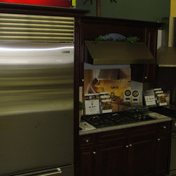 "Johnson Brothers TV and Appliance Kitchen Display Suites - This picture shows the Sub-Zero BI-36U/S/PH 36"" built-in Over-and-Under refrigerator with Pro handle, a Wolf CT36G/S 36"" gas cooktop and the Wolf DF364G 36"" dual-fuel pro range with griddle in the background."