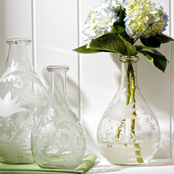 Etched Tear Drop Vases - Set of 3 - Curling tendrils of vine unite the silhouettes of young ferns and fan-shaped maple leaves in the engraved design of the Etched Tear Drop Vases. A beautiful and well-made trio in clear glass, shaped with a fine slender taper into their necks, these ethereal decorative bottles hold flowers, small fillers, or nothing at all with a handsome, well-coordinated look.