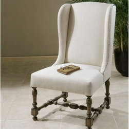 Uttermost Diella Alabaster Wingback Accent Chair - A traditional wingback design and Spanish style carvings make the Uttermost Diella Alabaster Wingback Accent Chair distinctive. Its solid hardwood frame and exposed, carved legs are finished in a deep walnut stain. To contrast, the chair is upholstered in alabaster linen with subtle slubbing and accented with antique bronze accent nails. About UttermostThe mission of the Uttermost Company is simple: to make great home accessories at reasonable prices. This has been their objective since founding their family-owned business over 30 years ago. Uttermost manufactures mirrors, art, metal wall art, lamps, accessories, clocks, and lighting fixtures in its Rocky Mount, Virginia, factories. They provide quality furnishings throughout the world from their state-of-the-art distribution center located on the West Coast of the United States.