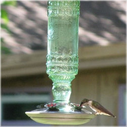 Avant Garden Antique Green Glass Hummingbird Feeder - Bring retro charm and a swarm of hummingbirds to your garden with the Avant Garden Antique Green Glass Hummingbird Feeder. This hummingbird feeder has a sea green antique glass bottle design with a brushed silver base, and sturdy hanger. It features four decorative flower feeding ports to attract and feed several hummingbirds at once. It holds up to 10 ounces of nectar and cleans up easily with soap and warm water.About WoodstreamWoodstream has been creating innovative garden, pet, and wild bird solutions for years. Since 1958 they've been crafting a unique line of wild bird feeders to make life more colorful for birders and easier for their feathered friends. Theyve done the research to design feeders that will entice more birds to your yard while adding style to your surroundings. Woodstream wild bird feeders come in a variety of sizes, shapes, finishes, and perch options. Youre sure to find the perfect gift for you or the birder in your life.