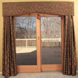 Patio Door Cornice and Drapery - Masterfully executed patio door curtains that consist of pinch pleat drapes and a cornice are made of pretty damask fabric. They frame the beautiful garden view from the kitchen. Olive green fabric works with the creamy paint colors.