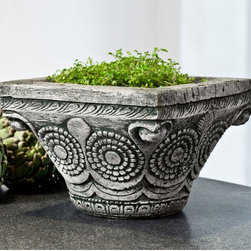 Campania International - Campania International Ostia Cast Stone Planter - P-632-AL - Shop for Planters and Pottery from Hayneedle.com! Petite yet bold the Campania International Ostia Cast Stone Planter proves that big things come in small packages. This planter features a unique squared top tapered base and is deeply etched with a stylized floral pattern. Scaled just right to fit within your indoor or outdoor setting though it's crafted of cast stone to withstand the elements. Comes in a wide variety of aged patina colors. Campania Cast Stone: The ProcessThe creation of Campania's cast stone pieces begins and ends by hand. From the creation of an original design making of a mold pouring the cast stone application of the patina to the final packing of an order the process is both technical and artistic. As many as 30 pairs of hands are involved in the creation of each Campania piece in a labor intensive 15 step process.The process begins either with the creation of an original copyrighted design by Campania's artisans or an antique original. Antique originals will often require some restoration work which is also done in-house by expert craftsmen. Campania's mold making department will then begin a multi-step process to create a production mold which will properly replicate the detail and texture of the original piece. Depending on its size and complexity a mold can take as long as three months to complete. Campania creates in excess of 700 molds per year.After a mold is completed it is moved to the production area where a team individually hand pours the liquid cast stone mixture into the mold and employs special techniques to remove air bubbles. Campania carefully monitors the PSI of every piece. PSI (pounds per square inch) measures the strength of every piece to ensure durability. The PSI of Campania pieces is currently engineered at approximately 7500 for optimum strength. Each piece is air-dried and then de-molded by hand. After an internal quality check pieces are sent to a finishing department where seams are ground and any air holes caused by the pouring process are filled and smoothed. Pieces are then placed on a pallet for stocking in the warehouse.All Campania pieces are produced and stocked in natural cast stone. When a customer's order is placed pieces are pulled and unless a piece is requested in natural cast stone it is finished in a unique patinas. All patinas are applied by hand in a multi-step process; some patinas require three separate color applications. A finisher's skill in applying the patina and wiping away any excess to highlight detail requires not only technical skill but also true artistic sensibility. Every Campania piece becomes a unique and original work of garden art as a result.After the patina is dry the piece is then quality inspected. All pieces of a customer's order are batched and checked for completeness. A two-person packing team will then pack the order by hand into gaylord boxes on pallets. The packing material used is excelsior a natural wood product that has no chemical additives and may be recycled as display material repacking customer orders mulch or even bedding for animals. This exhaustive process ensures that Campania will remain a popular and beloved choice when it comes to garden decor.About Campania InternationalEstablished in 1984 Campania International's reputation has been built on quality original products and service. Originally selling terra cotta planters Campania soon began to research and develop the design and manufacture of cast stone garden planters and ornaments. Campania is also an importer and wholesaler of garden products including polyethylene terra cotta glazed pottery cast iron and fiberglass planters as well as classic garden structures fountains and cast resin statuary.