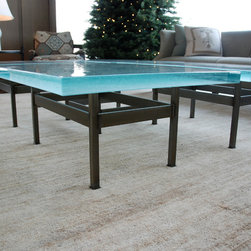 """The Four Square Coffee Table - This is a custom coffee table by Brandner Design. Hand made from solid steel bar, flawlessly welded and colored with a bronze acid patina. This table is topped with 2"""" slabs of blue glass."""