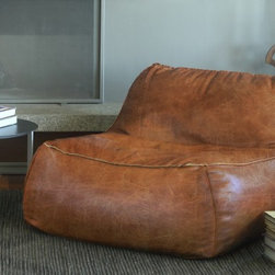 Lounge Chair in Rust Leather - Slow the pace and scout out your own private spot for laziness in the privacy of the backyard. Make the settee your outdoor headquarter for a day of reading and sneaking in a nap. Lounging on the couch has been taken to a whole new level. This versatile accent chair has many forms of use. The leather bean bag chair is extremely lightweight and can be easily transported from room to room. This leather beanbag chair also has a child-safe locking double zipper on the bottom.