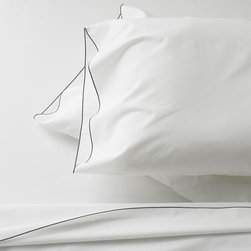 Belo Grey California King Sheet Set - Clean, basic white bedding upgrades in soft, smooth cotton percale, beautifully contrasted with a graceful grey overlocking stitch on the flat sheet and pillowcase. Generous fitted sheet pockets accommodate thicker mattresses. Sheet set includes one flat sheet, one fitted sheet and two pillowcases. Bed pillows also available.