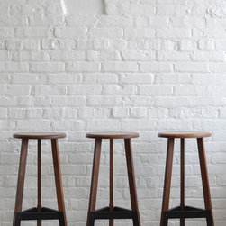 Poet stools - The three legs are connected to the seat using mortise and tenon joints. This method is as beautiful as it is durable. Craftsmen across the globe have been using this construction for ages. Formed steel connects each leg and provides the perfect spot to rest your feet.