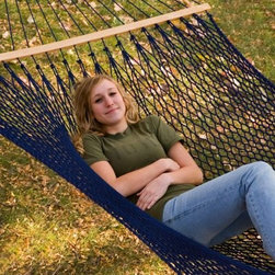 Twin Oaks Silk Spun Rope Hammock and Stand - make a relaxing retreat for yourself right in your own backyard with the Twin Oaks SilkSpun Rope Hammock package. This rope hammock is sized right for sharing because it will accommodate two people and up to 450 pounds of weight. It features top-quality materials like white oak spreader bars finished in natural linseed oil and super-durable SilkSpun rope. The stand is available in our exclusive wood grain finishes as well as the 5 best-selling solid color finishes - you choose. This rope is the same material found on other highly popular hammock brands like Pawley's Island. Solution-dying means it will not fade in the sun and the materials are mold- and mildew-resistant. This hammock lets you enjoy the comfort of cotton and the strength of polyester. The Material:This SilkSpun rope was maked to simulate both the strength and the softness of silk. It is twisted from a fiber especially manufactured for the outdoor market. This yarn has hundreds more filaments per inch than our standard rope, creating a denser, smoother result. Solution-dying results in longer-lasting, fade-resistant rope. The silky smooth SilkSpun product has an unsurpassed weather endurance and is mildew- and mold-resistant. The Construction: The traditional-style rope hammock has been reconstructed to increase comfort and durability. The body of the SilkSpun hammock features 50% more rows of rope and 50% more stitches per row than standard rope hammocks. This makes a bed with well over twice the standard number of stitches for a much closer weave. The result is added comfort and support. Available in several versatile finishes, this heavy-duty 14-gauge steel stand is capable of supporting any spreader bar hammock measuring 12 to 15 feet and up to 450 pounds of weight. The powder-coated finish is visually attractive and extremely weather-resistant. It assembles quickly without tools. About Twin Oaks HammocksAt Twin Oaks, we believe quality starts at the beginning - in every fiber of every rope and in every grain of every log. We start with yarn specially chosen for weather-resistance and colorfastness, and twist it into durable rope in all colors of the rainbow. Our spreader bars begin as locally-harvested white oak logs, which we mill and kiln-dry on site for well-seasoned outdoor use. The completed spreaders are hand-brushed with natural linseed oil and air-dried to maintain the beauty of the wood grain. Our macrame harnesses are made by hand, and carefully measured and trimmed so that every hammock we make is stable and comfortable. We weave each rope hammock ourselves, using techniques and equipment designed to be easy on the body and to minimize waste. Finally, at least 40 expertly tied bowline knots complete a hammock that is sturdy and attractive.