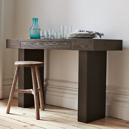 Terra Console - Strong, simple and eco savvy. A west elm green product, this minimalist multi-functional console table can also be used as a space-saving desk. (Its front conceals a hidden drawer.) The monolithic form is made from durable wood that's been certified as sustainably harvested by the nonprofit Forestry Stewardship Council (FSC) then finished with recycled-aluminum hardware and water-based stain and glues. A pure and perfectly proportioned addition to any room.