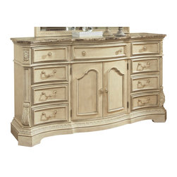 Signature Design by Ashley - Ortanique Dresser in Light Opulent - Upgrade your clothing storage with this traditional serpentine dresser. Its elaborate Old World design with natural marble parquetry top is a luxurious addition to your daily routine. Drawer fronts and the two center doors feature beaded molding and stepped molding. Canted corners feature acanthus leaf motifs that complement the ornate style of the trim and molding above the chests bracket feet. W ith full extension ball bearing side guides and fully finished drawer interiors this bedroom storage piece will be a delight to use. The Ortanique Dresser by Ashley Millenium is constructed for strength and quality using ash swirl and birch veneers with Asian hardwoods.