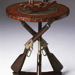 Butler - Accent Table in Mountain Lodge Finish - Mountain Lodge  finish. This distinctive accent table is sure to inspire the cowboy in us all. It features a ruggedly distressed top with an etched brass inset showing a riding cowboy scene, and a cast resin pedestal consisting of three lever action rifles supported on a wood base accented with coco twigs. 22 in. Dia. x 27.75 in. H