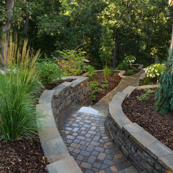 Side Yard Access - This walkway, constructed of pavers and modular wall block takes guests and neighbors to the newly-created backyard space, complete with fire pit and outdoor dining space.  At night, low-voltage lighting just under the walls caps illuminate the steps for safety....besides adding to the ambiance.