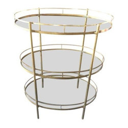 Pre-owned Mid-Century Brass and Glass Three Tier Bar Cart - This gleaming 1950s-60s classic is a Mad Men-era piece that has served it's share of Manhattans! It is in very good condition, with only a slight, almost unnoticeable bend in one section of the top rail. The glass on two shelves has a small chip on the very outer edge near the brass rail that is not noticeable. The third glass shelf is pristine. This elegant bar cart harkens back to glamorous times in New York, and will lend the same polish and sophistication to your gatherings.