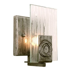 Varaluz - Polar Wall Sconce by Varaluz - Geosynchronous orbits and polar ice caps provide the unlikely inspiration for the warm and modern Varaluz Polar Wall Sconce. A halogen lamp shines like golden candlelight though a frosty pane of Ice Crystal glass. This panel is accented by a rustic metal base that's finished in Blackened Silver and adorned with minimalist circular detailing. ADA compliant.70% recycled steel, 100% recycled glass, 0% recycled style. Varaluz Lighting develops handmade fixtures created from recycled or reclaimed materials styled in a broad range of lighting genres from period to transitional and contemporary. Varaluz light fixtures that are like jewelry for the home, crafted to be relevant for generations.The Varaluz Polar Wall Sconce is available with the following:Details:Ice Crystal recycled glass plateRecycled metal baseBlackened Silver finishSquare wall plateADA CompliantUL ListedLighting:One 50 Watt 120 Volt Type G9 Halogen lamp (included).Shipping:This item usually ships within 5-7 business days.