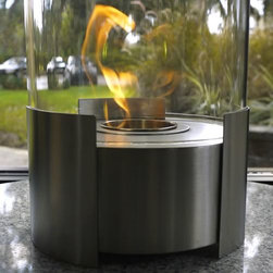 Caldo Tabletop Bio Ethanol Fireplace by Nu-Flame - Caldo, cylindrical in shape, is ideal for creating emotional decor. Providing a 360 degree view of the dancing flame, Caldo provides comforting warmth in a small space or patio. This fireplace offers an eco-friendly flame that is odorless. Bio Ethanol, an alternative fuel source produced from plants, only emits water vapor and carbon dioxide into the air. Although ethanol fireplaces aren't intended for use as a primary heat source, the Caldo model produces some heat that will change the ambient temperature in a small space. For aesthetic appeal and safety, this fireplace includes a piece of tempered glass that surrounds the flame and provides the unobstructed view. Appropriate for any space, indoors or out, Caldo's base is offered in a grey powder-coat.