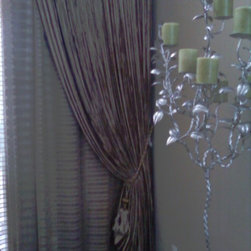 Some of our work - This 12 foot wide by 16 foot high double window is covered in a striped sheer pinch pleated drape and a beautiful warm velvet drape in front to act as an accent panel that is fully operational for privacy at night.