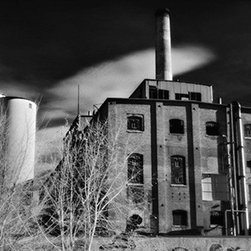 """Sugar Factory, Longmont - Large-Scale, Limited Edition Photography - There are great shapes throughout this large format, 28"""" x 18"""" fine art photograph. The imagery and textures provided by the old brick buildings shed light on industrial Colorado. The strange sky provides great depth behind the buildings and is a wonderful background for the entire portrait."""