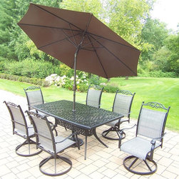Oakland Living - 9-Pc Dinning Set in Black - Includes boat shaped table, six swivel rockers, 9 ft. tilt crank umbrella with stand and metal hardware. Traditional lattice pattern and scroll work. Hardened powder coat. Handcast. Fade, chip and crack resistant. Warranty: One year limited. Made from cast aluminum and sling. Minimal assembly required. Table: 70 in. W x 38 in. D x 29 in. H (75 lbs.). Swivel Chair: 24 in. W x 30.5 in. D x 40 in. H (16 lbs.)The Oakland cascade collection combines southern style and modern designs giving you a rich addition to any outdoor setting. We recommend that the products be covered to protect them when not in use. To preserve the beauty and finish of the metal products, we recommend applying an epoxy clear coat once a year. However, because of the nature of iron it will eventually rust when exposed to the elements.