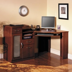 Bush Vantage Cherry Corner Computer Desk - The Bush Vantage Cherry Corner Computer Desk is the stylish convenient answer for all of your office needs. The elegant harvest cherry finish enhances most decor while the corner-style design makes convenient placement options. It features three drawers one for files and two for supplies or miscellaneous items. Complete with CPU storage and concealed wire access. (Note: CPU cabinet can only be placed on the left side.) An elevated printer shelf and additional adjustable removable shelf makes customization easy. Two drawers can hold supplies and miscellaneous storage while a file drawer is meant for holding letter-size files. An elevated shelf is also built in - this is great for a printer or other peripherals. Assembly required. Dimensions: Overall: 58.5W x 38.5D x 35.5H inches From back edge to left front edge of desk: 19.375 inches From back edge to right front edge of desk: 38.5 inches Work surface from front curve to back corner: 39.06 inches Knee well space: 29.72W x 25.06H inches Printer shelf: 23.375W x 21.375D inches CPU cabinet: 10.875W x 19.5D x 25.5H inches About Bush FurnitureBush Furniture is the eighth largest furniture company in the United States. Bush manufactures high-quality products which are designed to be easily assembled and provide great value for the price. Bush furniture is made from a combination of particleboard fiberboard and solid wood components. The use of real wood components will be noted in the product description if applicable. Bush Industries has over 4 000 000 total square feet of manufacturing warehousing and distribution space. This allows for a very wide selection of high-quality furniture with the ability to ship quickly. All standard residential Bush products carry a generous 6-year warranty. All Bush business furniture including the A series C series and Quantum series is backed by a 10-year warranty from Bush one of the best in the industry.