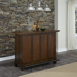 HomeStyles - Chestnut Bar - Our Cabin Creek collection conveys a reclaimed wood vintage feel. Each piece is physically distressed by hand, providing a unique one of a kind look. The Cabin Creek Bar is constructed of hardwood solids and veneers in a heavily distressed multi-step chestnut finish featuring worm holes, fly specking, small indentations, and season splitting. Bounteous storage is provided with two storage drawers, hanging stoneware storage, bottle storage, two adjustable shelves, and one fixed shelf. Other features include full length triple leg supported by metal foot rail in antiqued brass with rubbed brass highlights. Drawers are completed with hand forged replicated hardware. Assembly required. 56 in. W x 23.75 in. D x 42 in. H