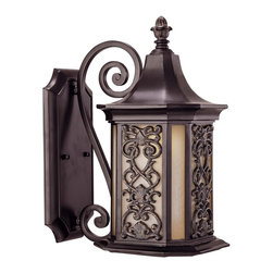 Forsyth Wall Mount Lantern - This Mediterranean style collection features an intricate six-sided geometric panel delicately placed over Tuscan glass with graceful scrollwork – all combining to perfect this die-cast collection. Como Black w/ Gold Finish.