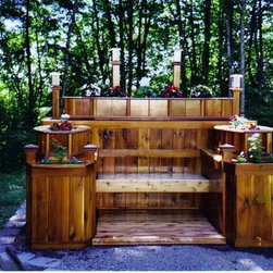 Custom Built Romantic Settings - When building custom benches, as an artist, one of the major considerations you should keep in mind is the customers personality. This customer was having their 35th wedding anniversary and both of them love gardening. This romantic center was built with several planter boxes at different levels surrounding the bench and incorporates several key features such as: drainage systems, water proof cabinets behind the bench, storage shelves, solar lights and a cedar landing. All of which was built with reclaimed cedar from repurposing a fence and deck.