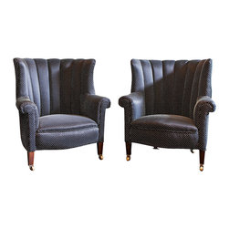 Christa Pirl Furniture - Consigned of Neoclassical Channel Back Armchairs Newly Upholstered - A handsome pair of petite and highly refined Georgian antique wingback chairs, circa 1820.  Clad in suits of bespeckled black, these gentlemen project a classic profile.  As a class, wingback chairs are somewhat atypical in that their shape remained largely unchanged for several centuries.  These chairs just barely reveal their English Neoclassical pedigree through their linear channel backs and subtly splayed wings.  Whiskey and cigars anyone?