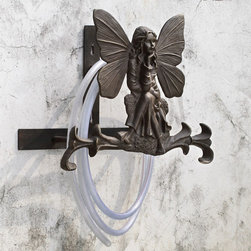 "Fairy Garden Hose Holder - Very contemplative, this little garden fairy. With her wings spread wide and her face the picture of peacefulness, she sits atop a stone on a scrolled base and keeps your hose in a tidy loop. Aluminum and wall attached. Dimensions: 17""w x 8.5""d x 14""h"