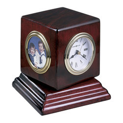 Howard Miller - Howard Miller Reuben Table Top Clock - Howard Miller - Mantel / Table Clocks - 645408 - This contemporary table clock is much more than just a timepiece with additional hygrometer thermometer and picture frame on adjacent sides of it's hardwood cube frame. Triple-rim brass tone bezels and a deeply molded base add further character to the Reuben while a Rosewood hall finish and protective felt bottom pair with battery-operated quartz movement to complete the appeal of the Reuben Table Top Clock.