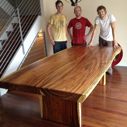 "Natural Edge Dining Table, 50"" x 96"" x 4"" thick - This custom made dining table for an Impact Imports client in the Northern Liberties section of Philadelphia measures 48-52"" wide x 8' long x 4"" thick and the table top alone weighs 450 lbs.  It is made from 2 pieces of monkeypod wood and the pieces are book matched.  The legs are also monkeypod wood, and to raise the table to our client's desired heights, we use 1"" diameter bolts, (screwed into double nuts set with resin in the legs) allowing us to add 1 more inch to the overall height.  This is a beautiful, 'last-a-lifetime' dining table!"