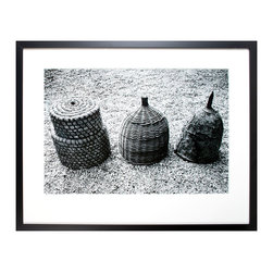 Luxembourg Three - Framed Print - Standing in a bed of cracked gravel, the artisan trio photographed for Luxembourg Three takes on a timeless aspect, serving as a monument to handicraft in traditional cultures. Enclosed within the white field of a wide mat and bounded by a narrow black wood frame, this detailed print is a stunning study in contrasting textures, ranging from strewn pebbles to basket weaving to cracked earthenware.