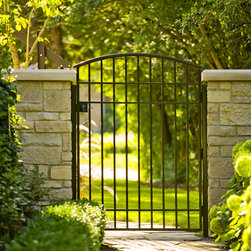 Deerfield Residence - Designed by: Marco Romani, RLA. Landscape Architect--- Custom Wrought Iron Gate, Sideyard Landscape, Masonry Wing Walls to Match House Stone and Lush Vegetation as an inviting entrance to the Rear Yard.